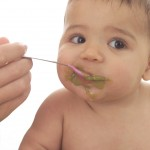 Photo of baby eating baby food.