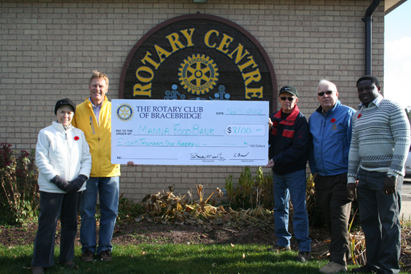 Manna volunteers accept $8,100 donation from the Rotary Club of Bracebridge.