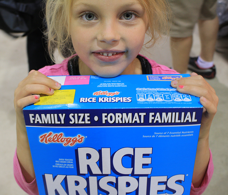 Young girl holding box of Rice Crispies.