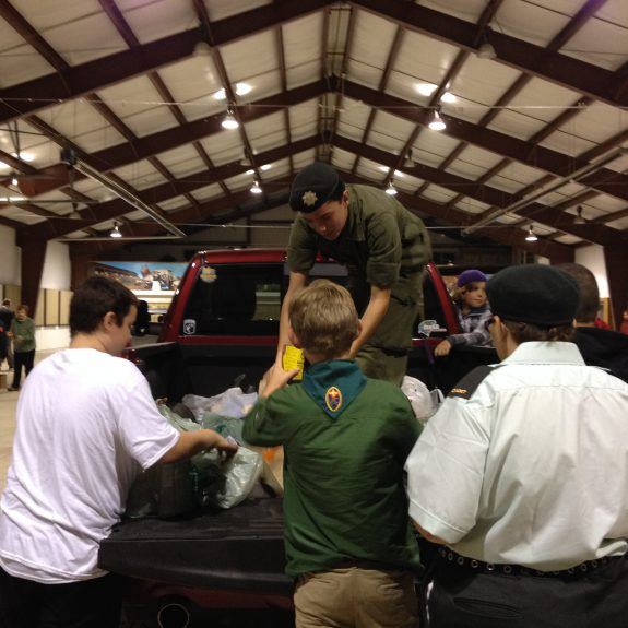 Volunteers unload donated food from a vehicle at the Fairgrounds