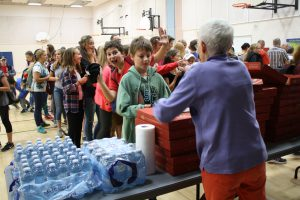 Manna president Sam Robinson serves the kids pizza. Nice photo bomb, Aiden!