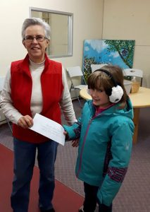Erica Meadows presents a cheque to Manna volunteer Barb Rowlinson
