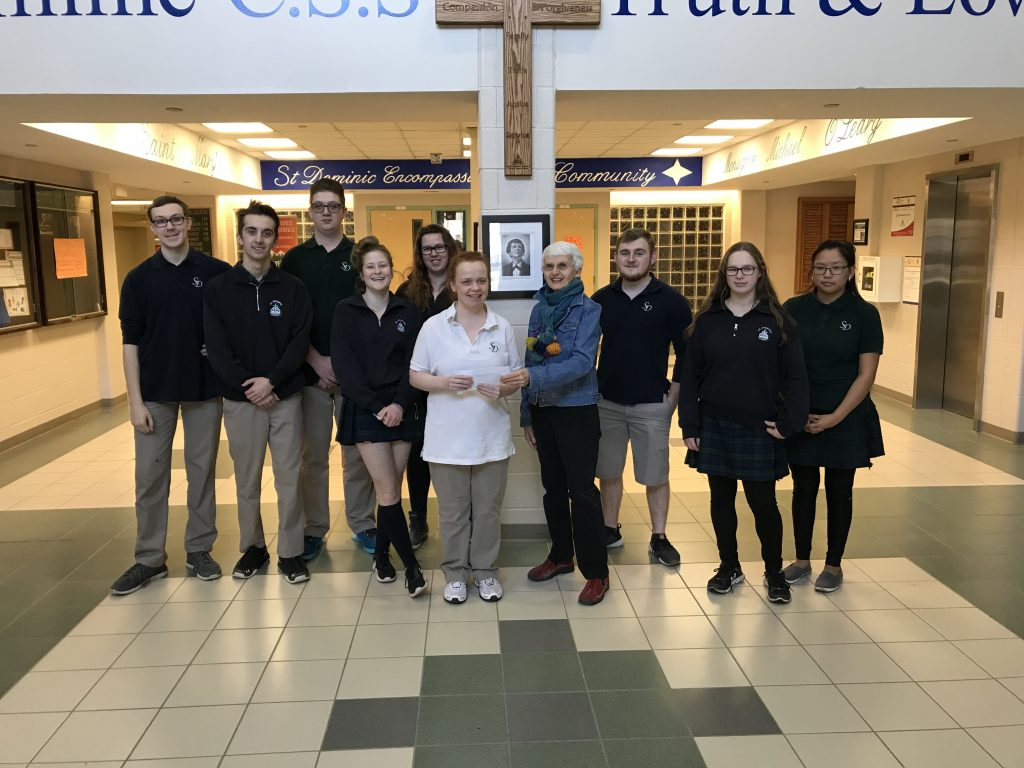 St. Dom's students presenting cheque to Manna