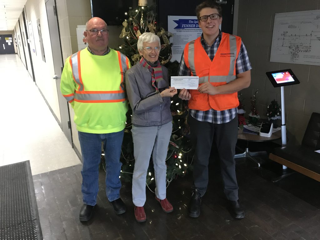 Matt Hausen and Bob Byrne present a cheque to Manna volunteer Sam in front of their holiday tree.