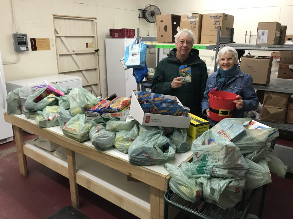 Manna volunteers Earle and Sam at the Manna Food Bank with donated food.