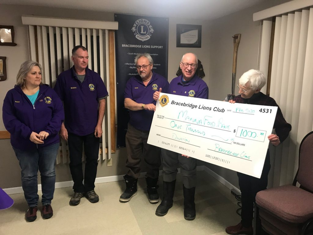 Four members of the Bracebridge Lions present a large cheque to Manna volunteer Sam.