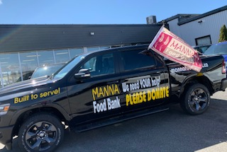 A very clean black truck with Manna Food Bank Please Donate written on the side.