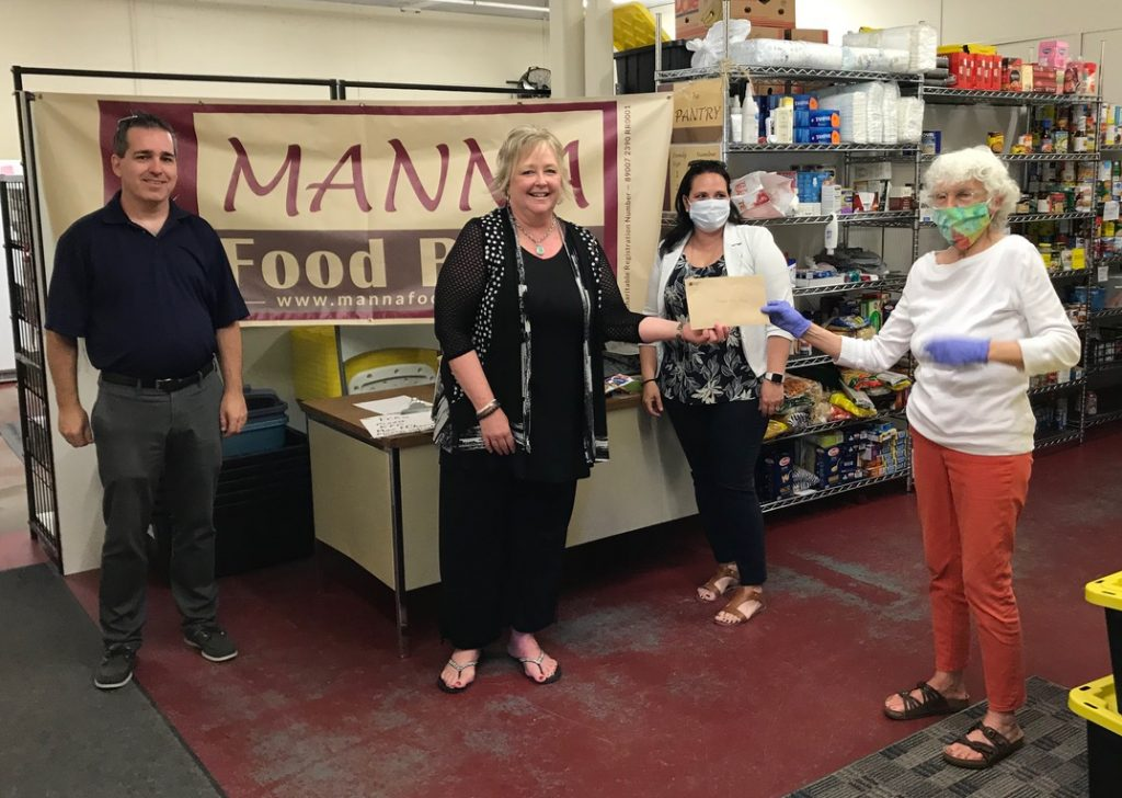 Picture of Chris Etherington and Julie Bissonette of Bracebridge and Cindy Harris of Barrie offices of IG Wealth Management, presenting cheque to Manna volunteer Sam.